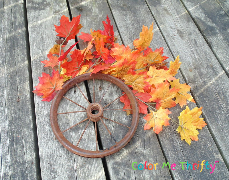 gluing plastic fall colored leaves onto wheel