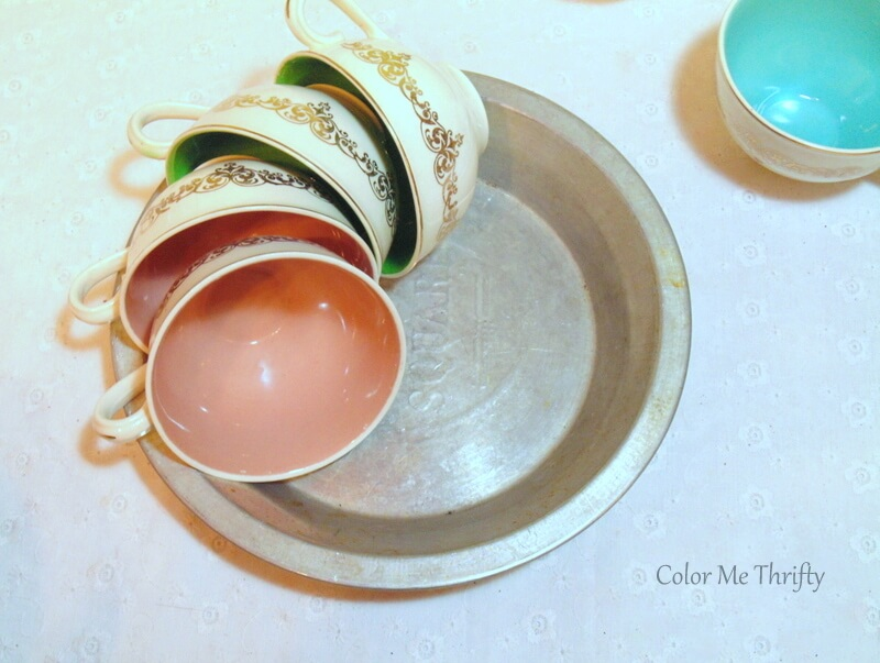 laying vintage teacups in a circle inside baking pan