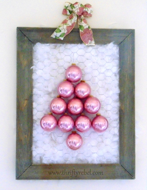 Vintage Christmas ornaments displayed on barnboard and chicken wire frame