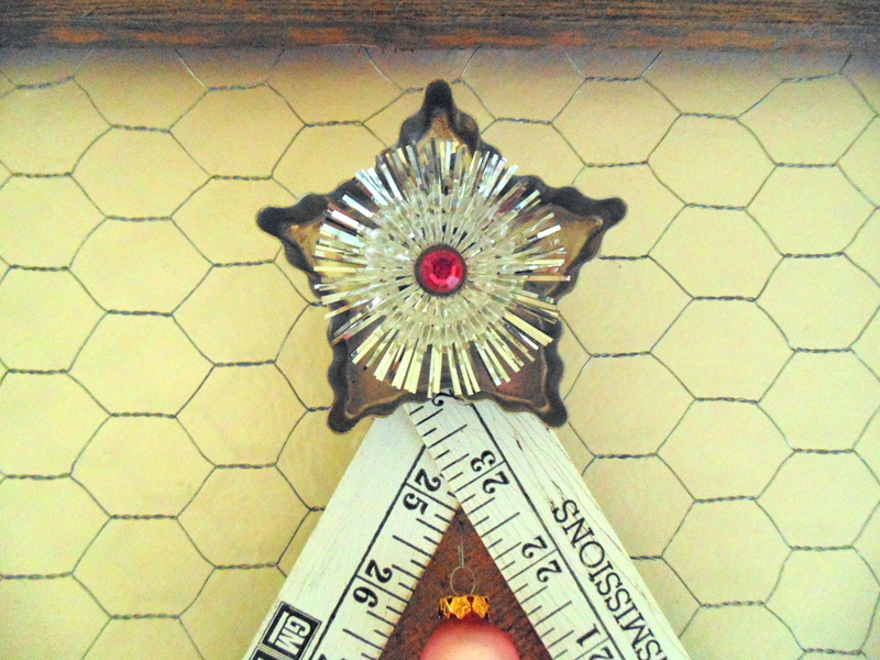 Vintage star cookie cutter and silver light reflector used as star of Folding Ruler Christmas Tree