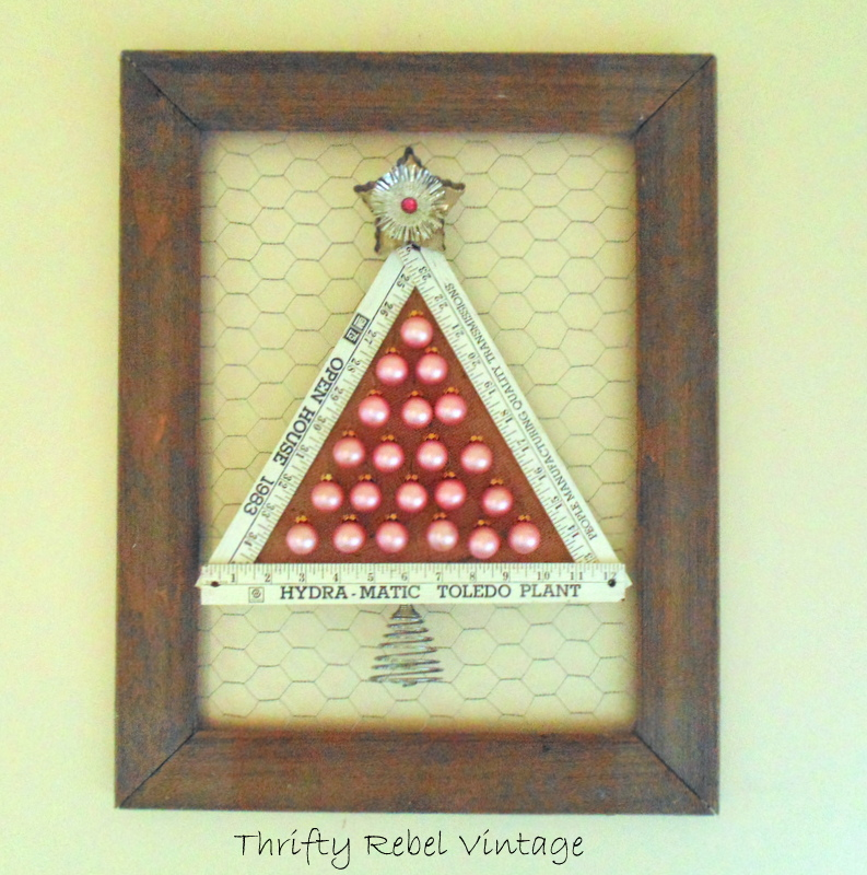 Repurposed Folding Ruler Christmas Tree with burlap back and miniature hanging ornaments on barnboard and chicken wire frame