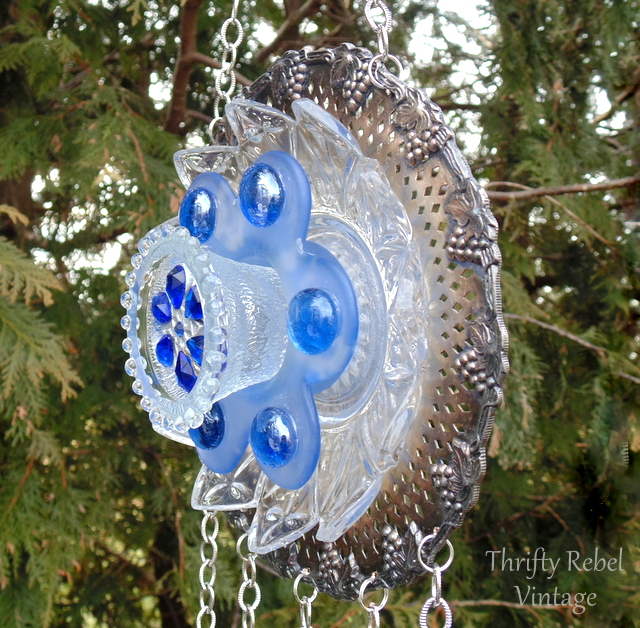 Side view of silver and glass plate flower and silverware wind chime