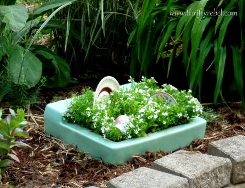 vintage green porcelain sink repurposed into planter with white lobelia and dishes