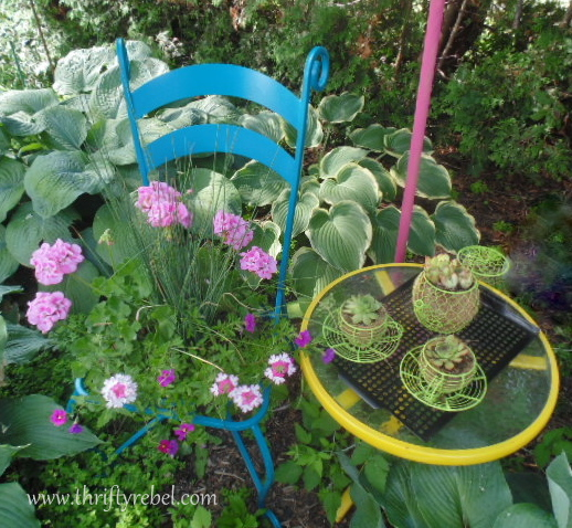 vintage metal chair repurposed as garden planter in garden cafe vignette