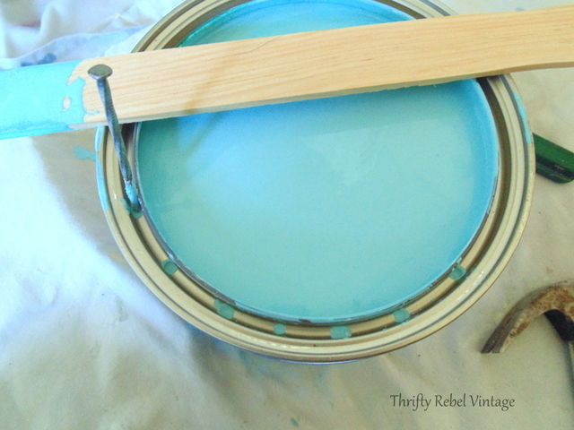 hammering holes into inside paint can rim to let excess paint drip back into can