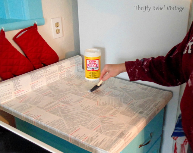 applying coat of mod podge on kitchen counter / thriftyrebelvintage.com