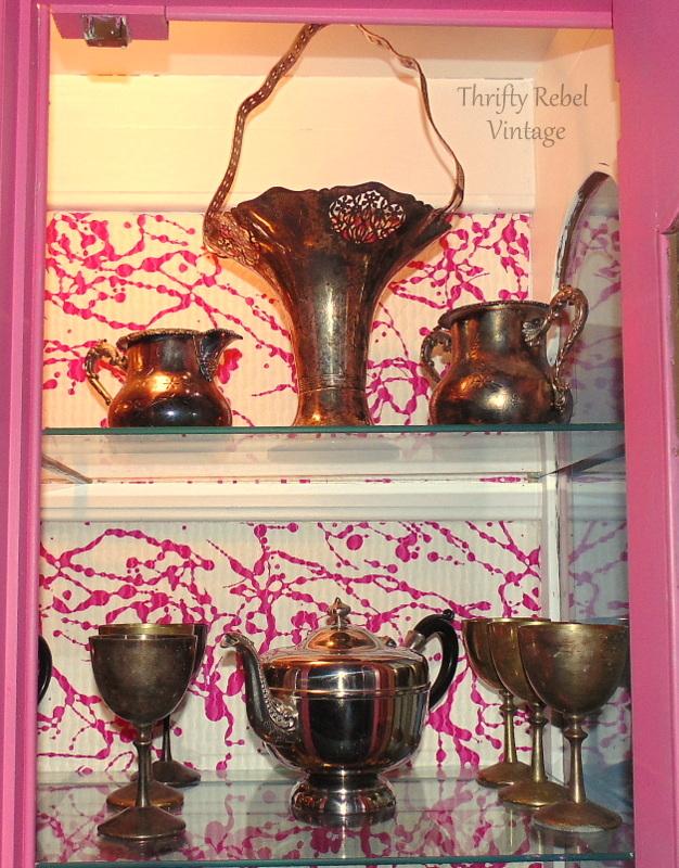 silver basket vase in china cabinet