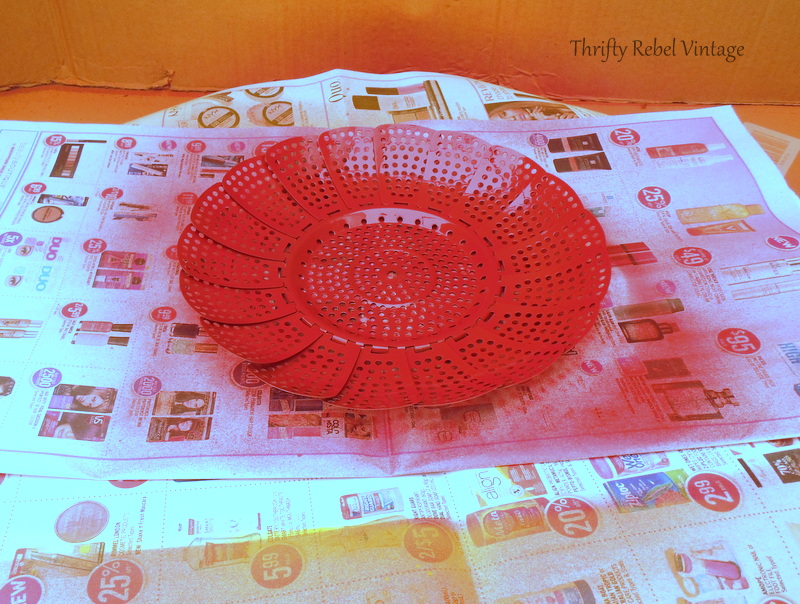 spray painting repurposed folding strainer flowers