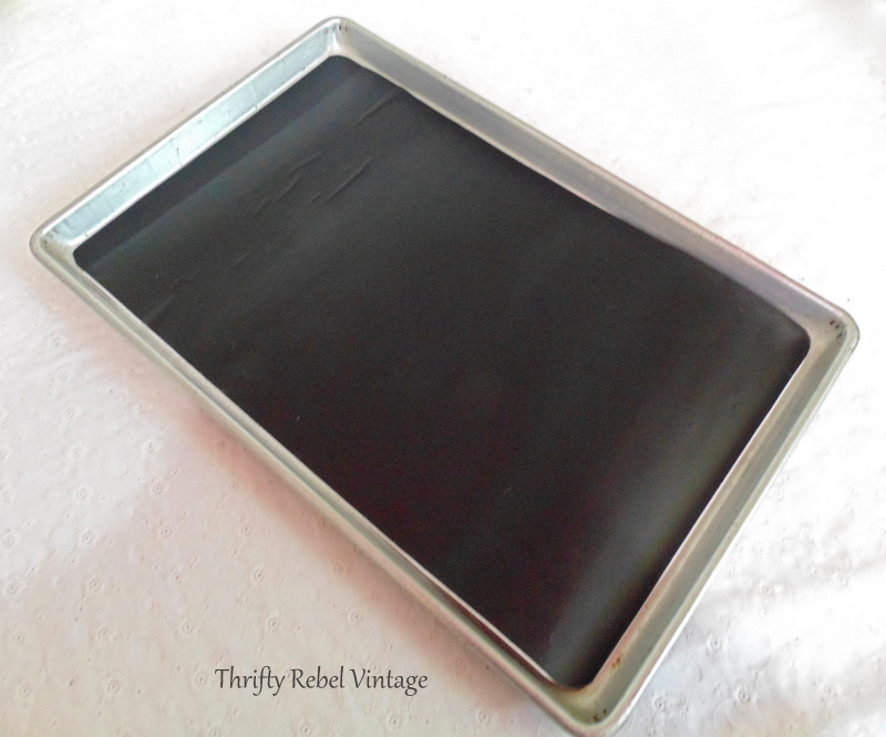 Placing chalkboard vinyl to make vintage cookie sheet chalkboard
