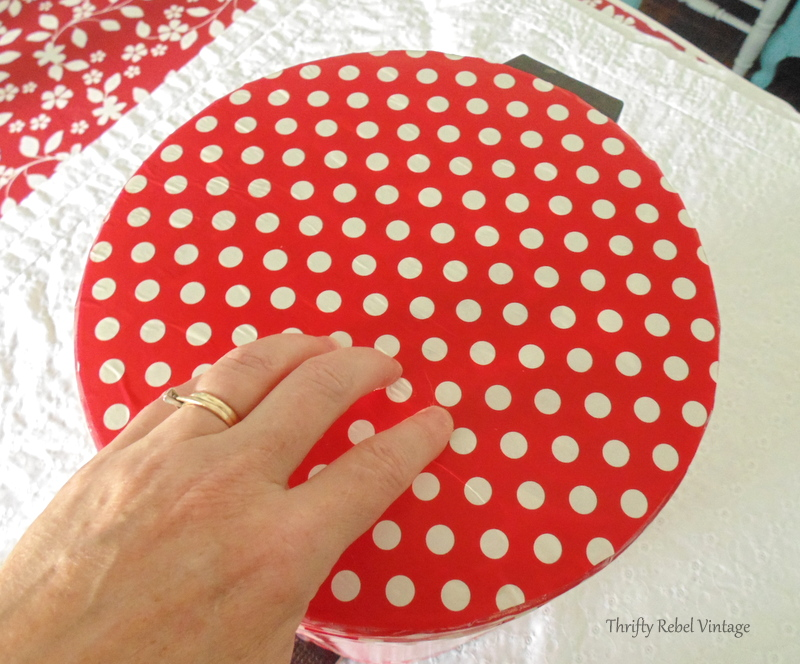 Applying round lid gift wrap piece for how to decoupage a garbage can