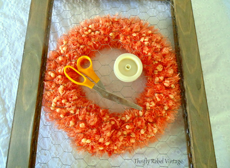 fishing line used to attached scarf wreath to chicken wire frame for fall door decor