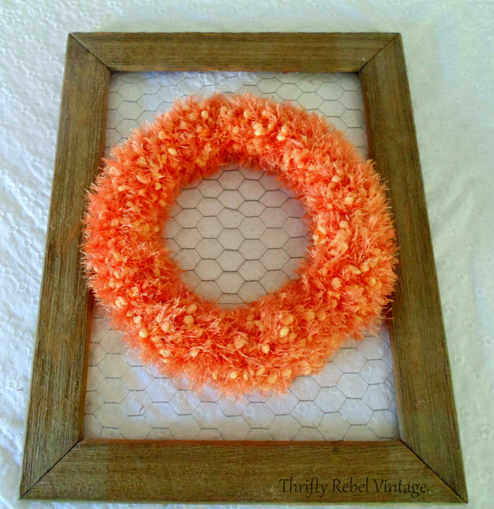 orange scarf wreath attached to chicken wire on rustic frame for fall door decor