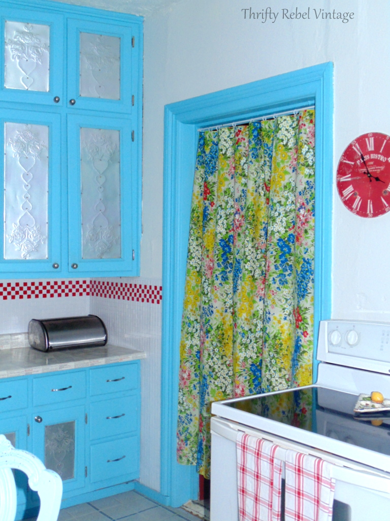 Floral tablecloth used as door curtain in red and aqua kitchen makeover