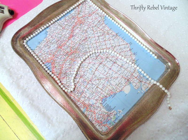 repurpoased necklace being glued onto decoupaged silver tray map table