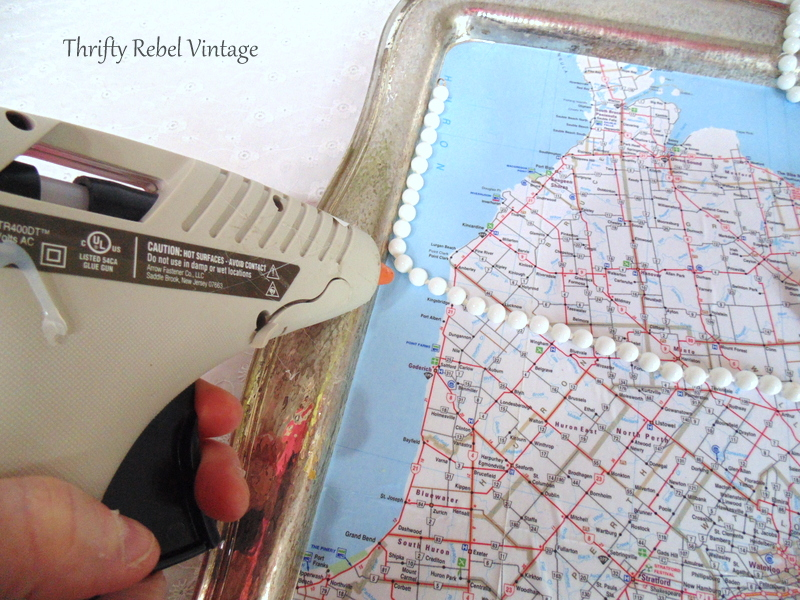 using glue gun to apply necklace for decoupaged silver tray map table