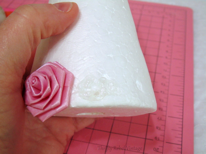 gluing miniature roses to styrofoam cone for miniature rose Christmas tree