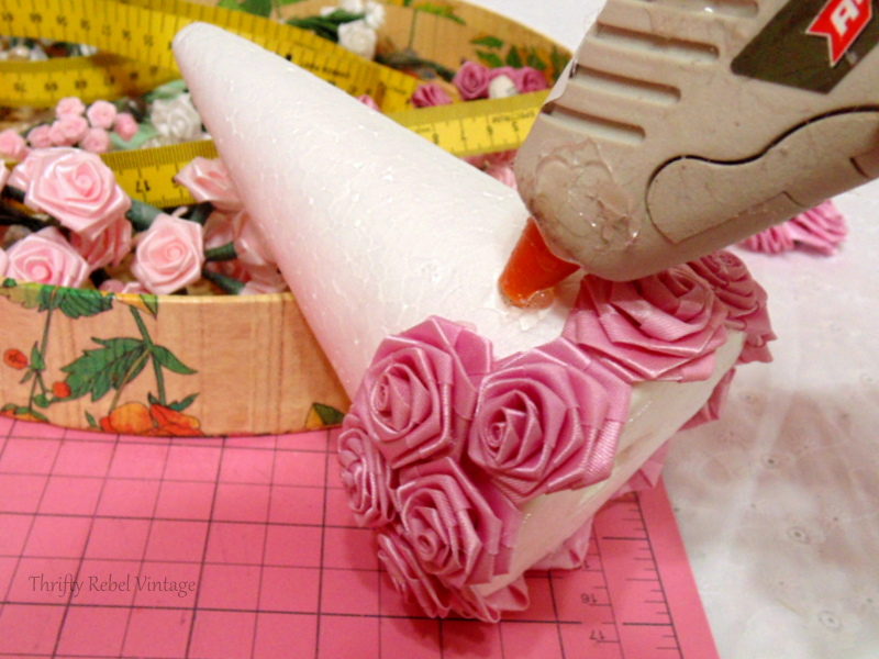 gluing more miniature roses on styrofoam tree cone for miniature rose Christmas tree