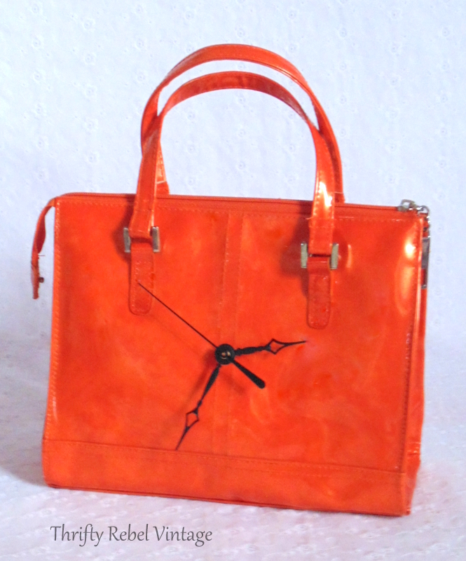 orange vinyl purse clock with black clock hands