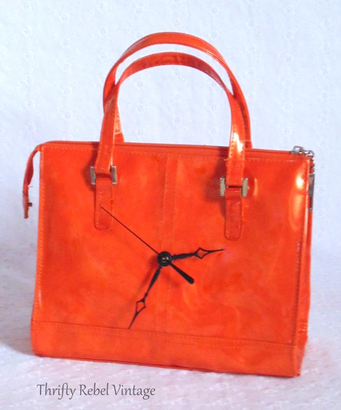 orange vinyl purse clock with black clock hands