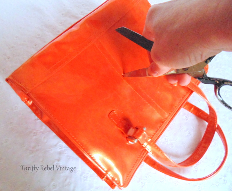 putting hole in orange purse with scissors to insert clock work mechanism