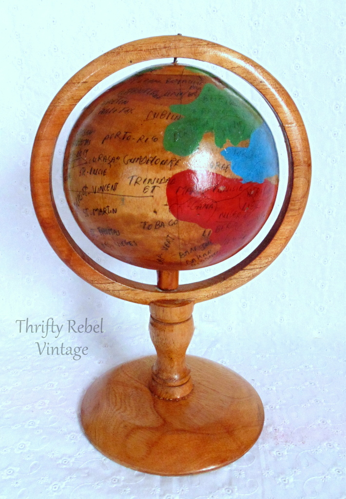 small handmade wooden globe on a pedestal