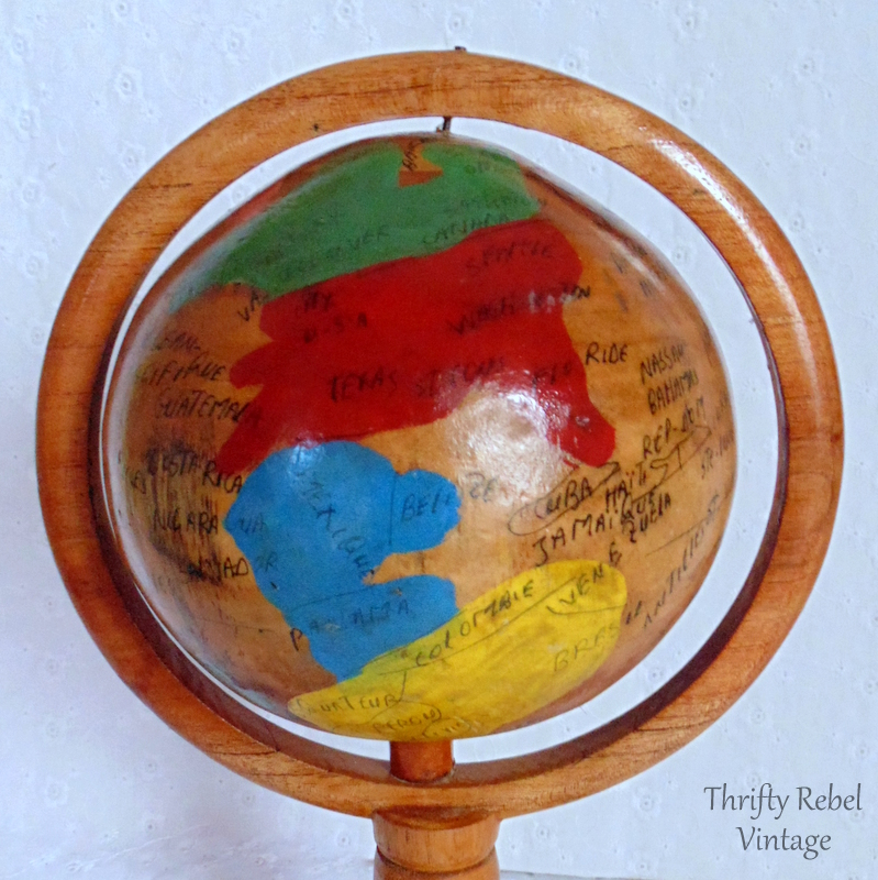 close up of small handmade wooden globe on a pedestal