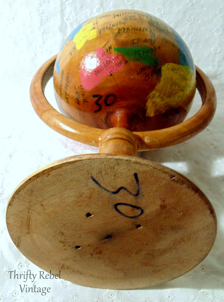bottom of small handmade wooden globe on a pedestal