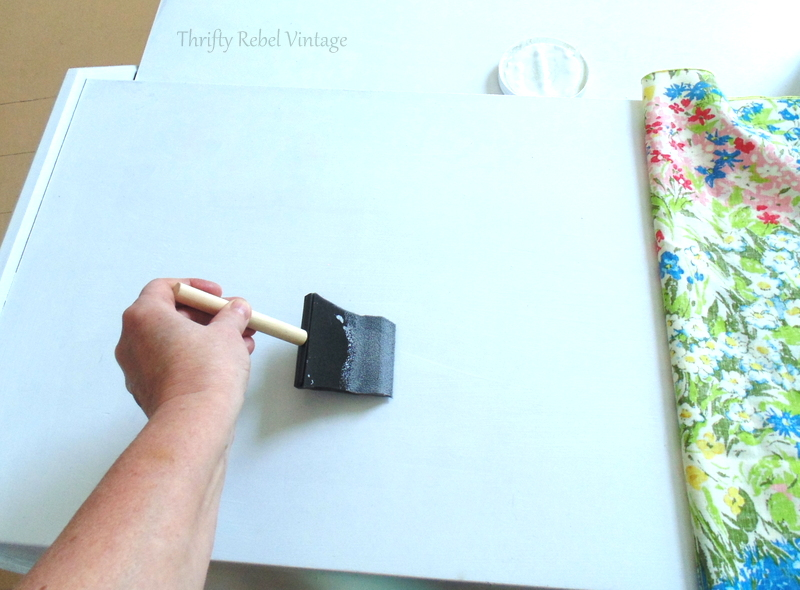 applying mod podge onto desk for fabric decoupaged desk makeover