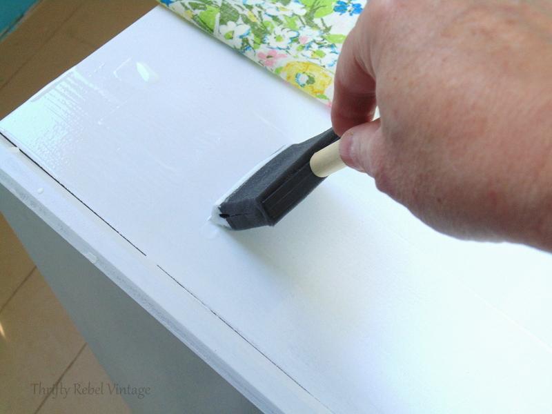 applying mod podge onto desk for fabric decoupaged desk makeover