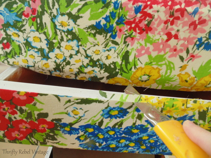 trimming floral fabric that was decoupaged on to desk drawers