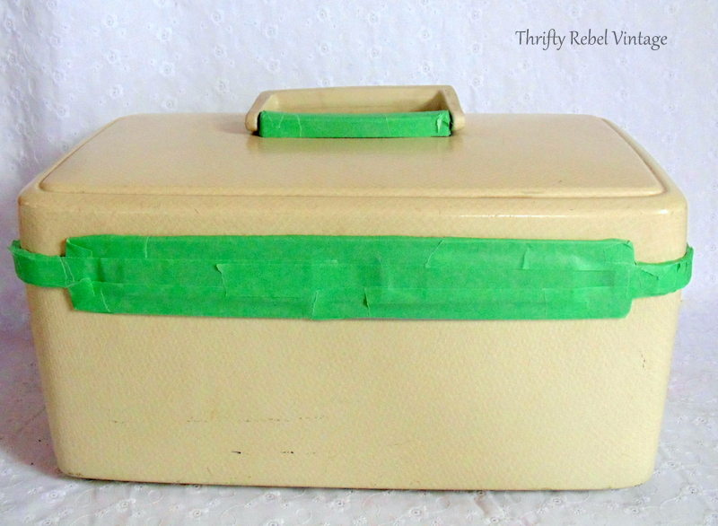 taping over metal parts of vintage cosmetic case exterior before spray painting