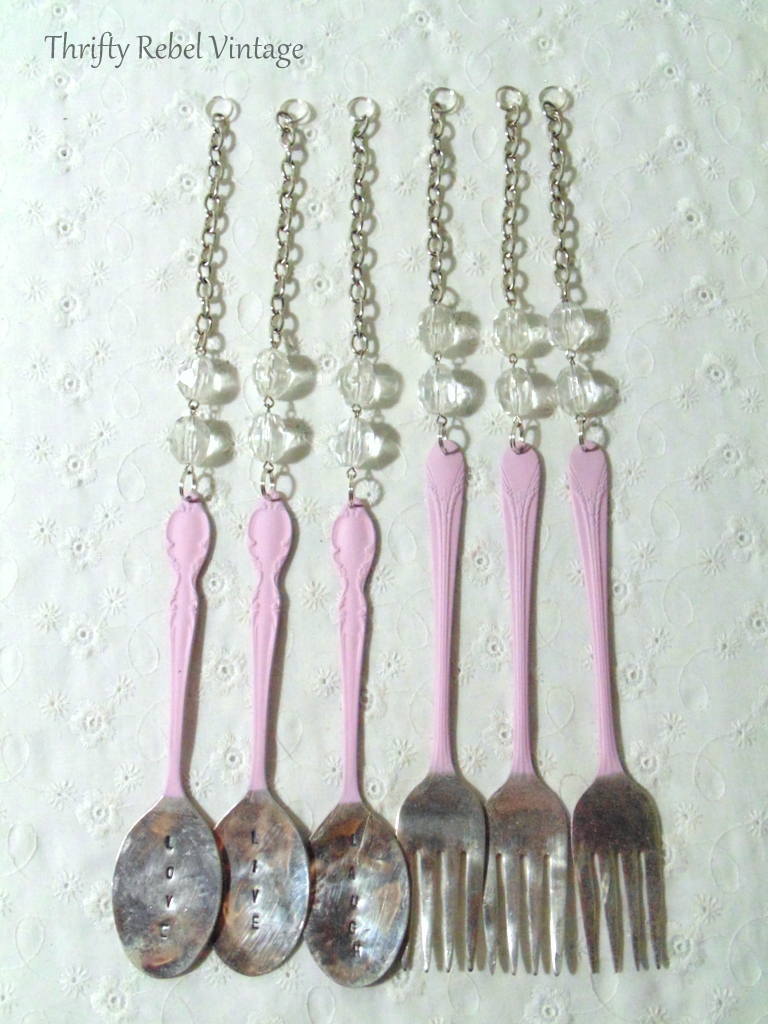 spray painted silverware hanging from repurposed necklace parts for diy wind chime