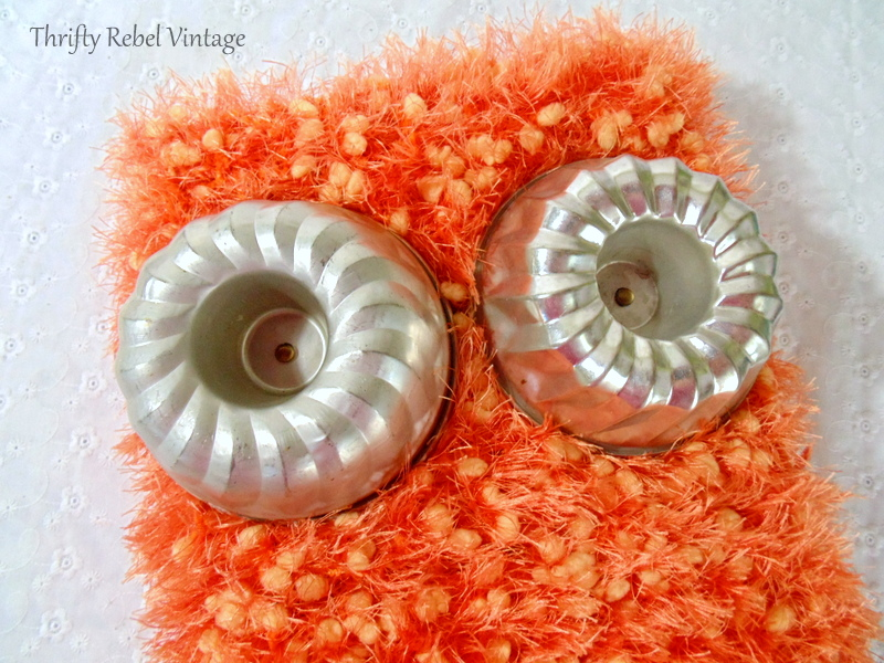 Jello mold owl eyes in place over orange scarf and aluminum baking pan