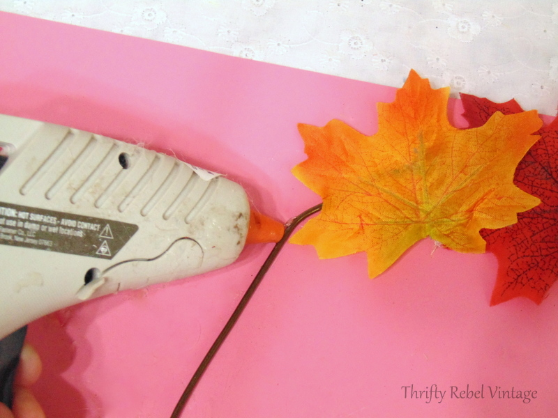 gluing faux leaves onto hanger with hot glue gun for quick and easy fall wreath