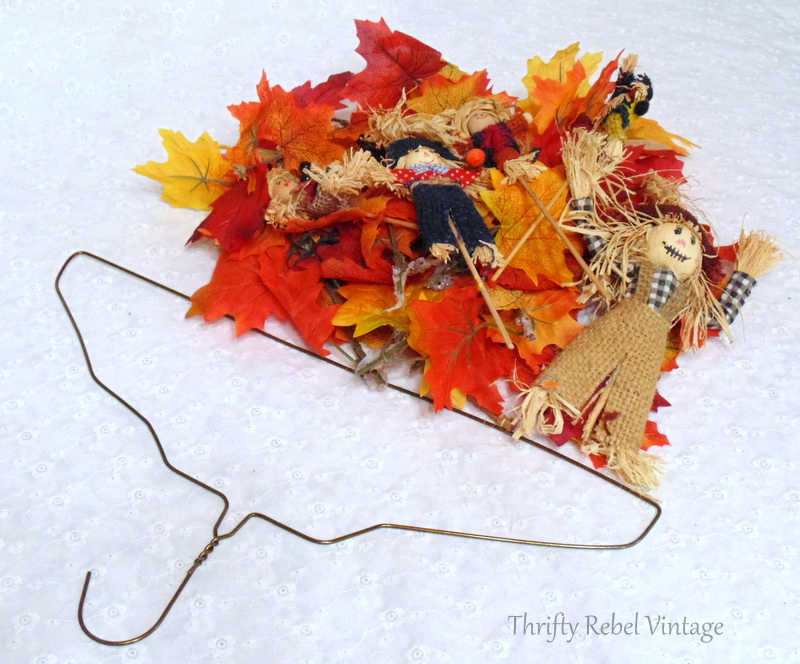 metal hanger, scarecrows, and faux leaves for quick and easy fall wreath