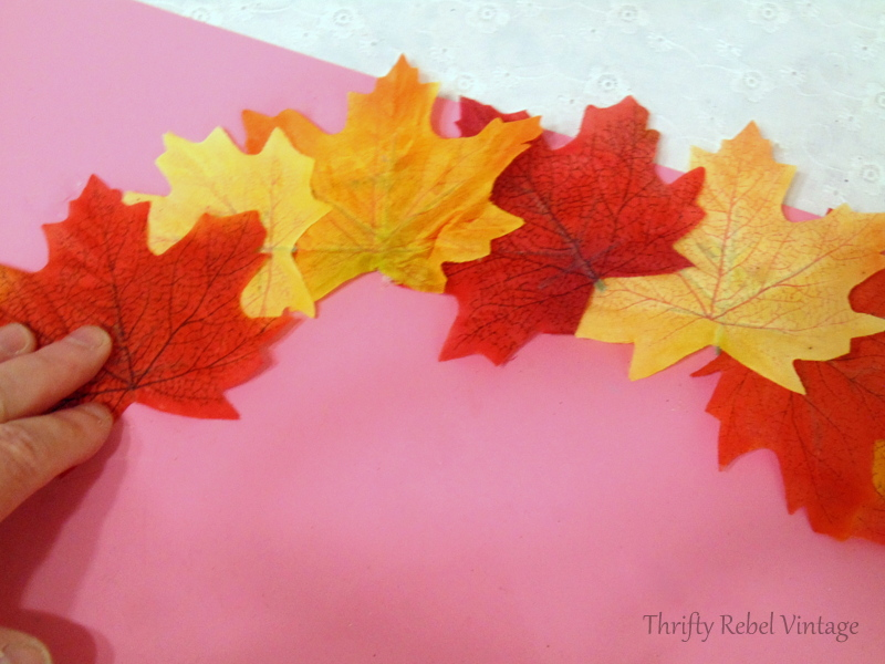 pressing down faux leaves when gluing onto hanger for quick and easy fall wreath