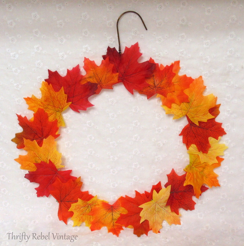 repurposed hanger fall wreath with faux leaves attached with hot glue gun