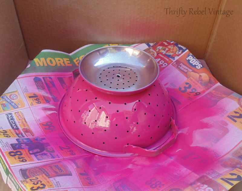 spray painting large strainer pink for diy tiered stand