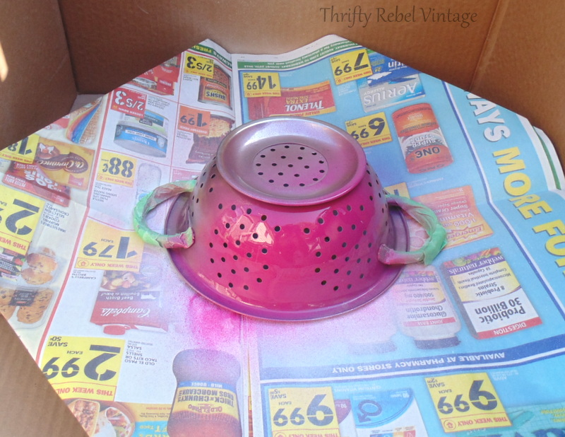 spray painting small strainers pink for diy tiered stand