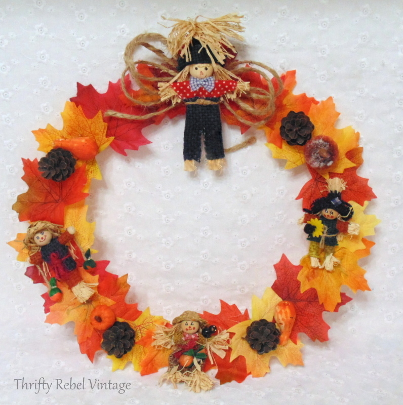 Glued mini scarecrows and pine cones onto faux leaf wreath
