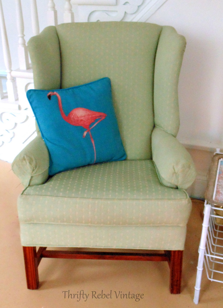 Green wing chair with aqua and pink flamingo pillow