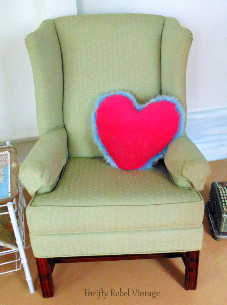Green wing chair with pink heart pillow with blue feather fringe