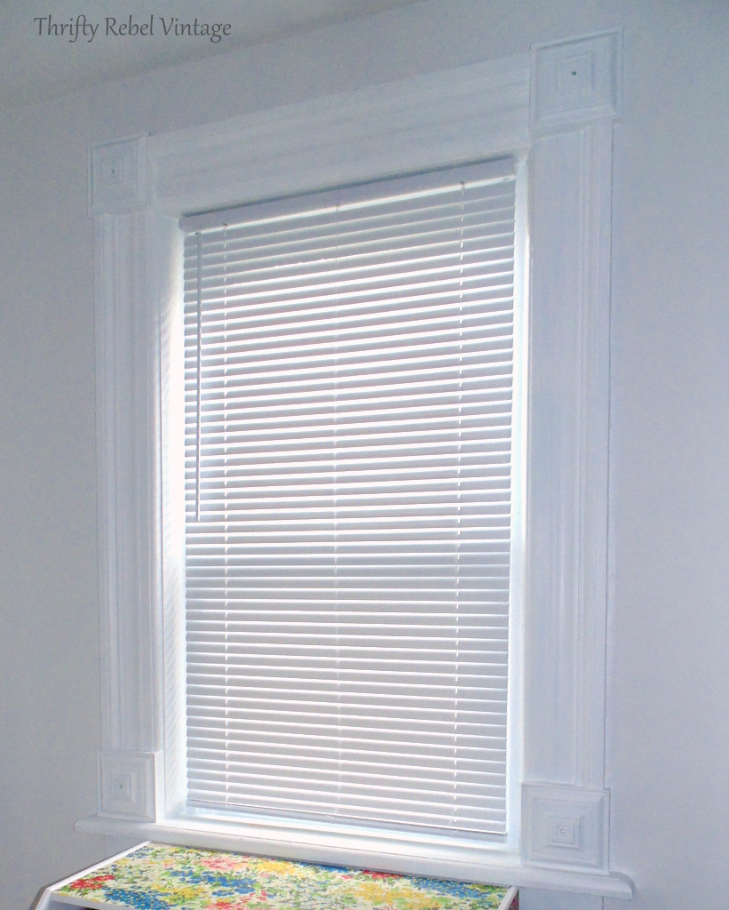 living room window with plain white vinyl mini blind