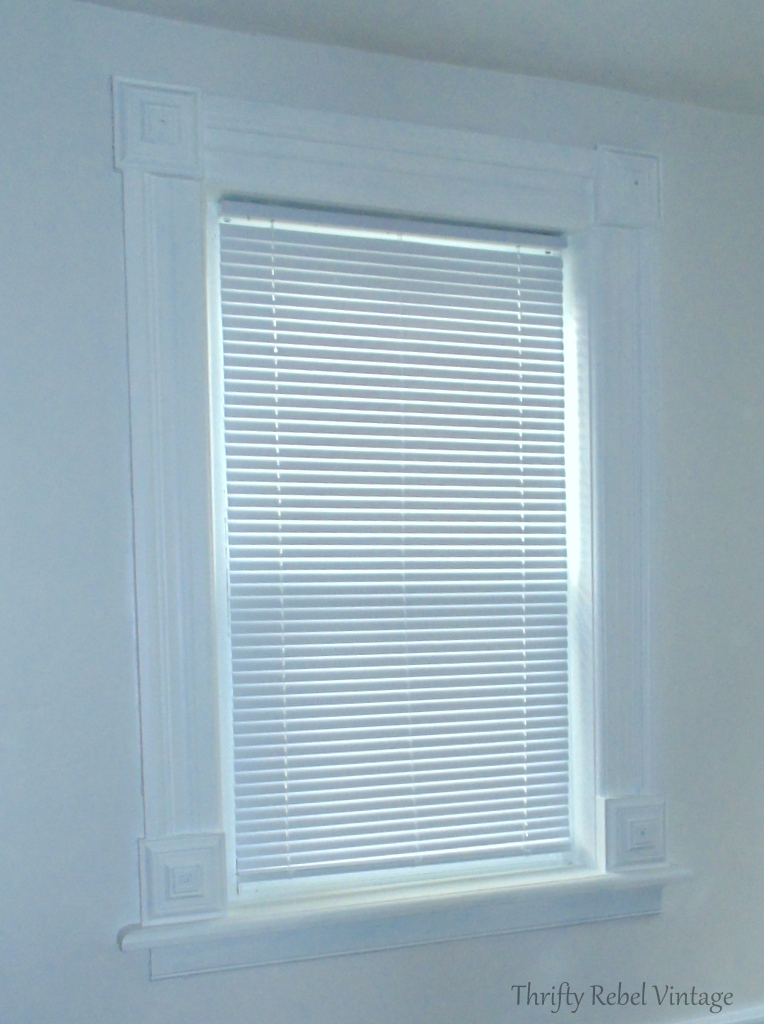 living room window with plain white vinyl mini blind