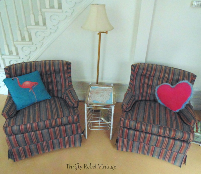 Pair of blue and pink striped swivel living room chairs with pillows