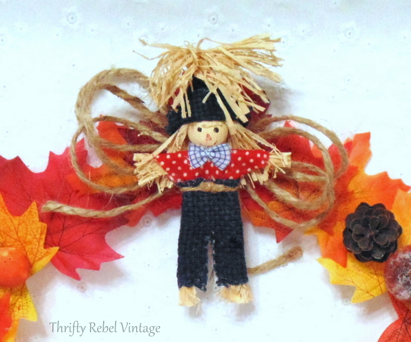 Glued mini scarecrow onto jute twine bow on fall wreath