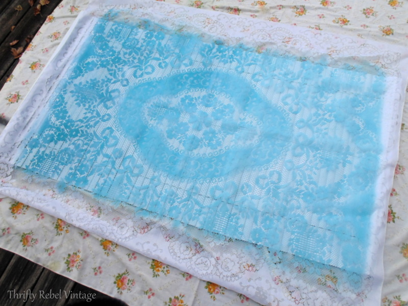 spreading lace tablecloth over vinyl mini blind for spray painting