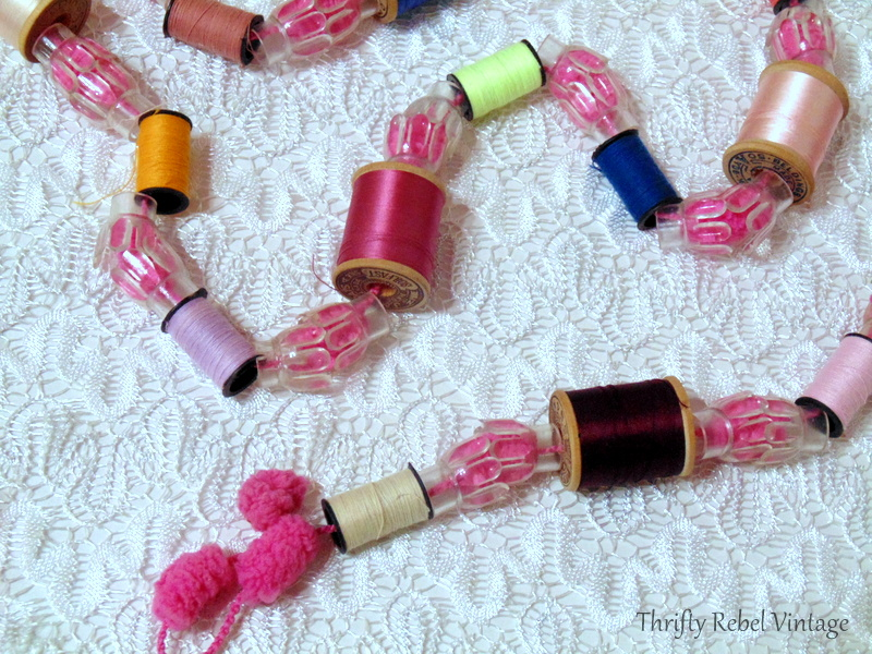 Repurposed thread spools garland on puff ball yarn with light reflectors 1
