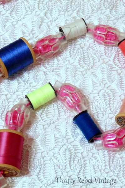Tree garland made using repurposed thread spools and clear light reflectors on puff ball yarn
