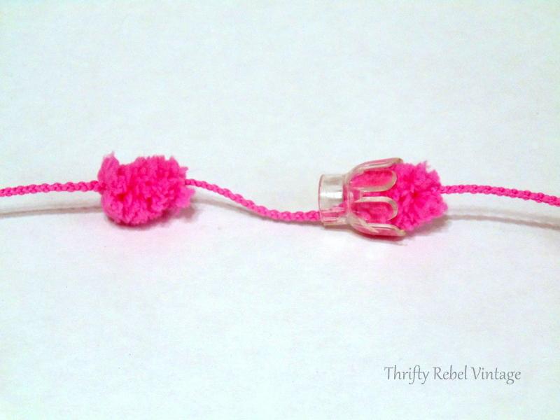 clear Christmas tree light reflectors threaded onto pink puff ball yarn